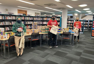 Three workers from the Fit, Fed and Read programme in a Redbridge library