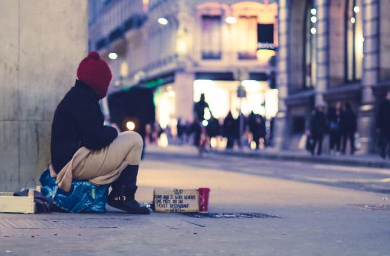 homeless person begging on the street in winter