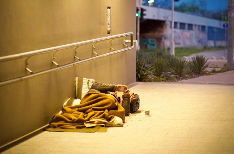 Man sleeping in a sleeping bag on the floor of an underpass