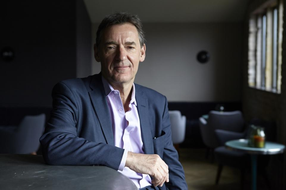 Jim O'Neill sat at a table looking into camera