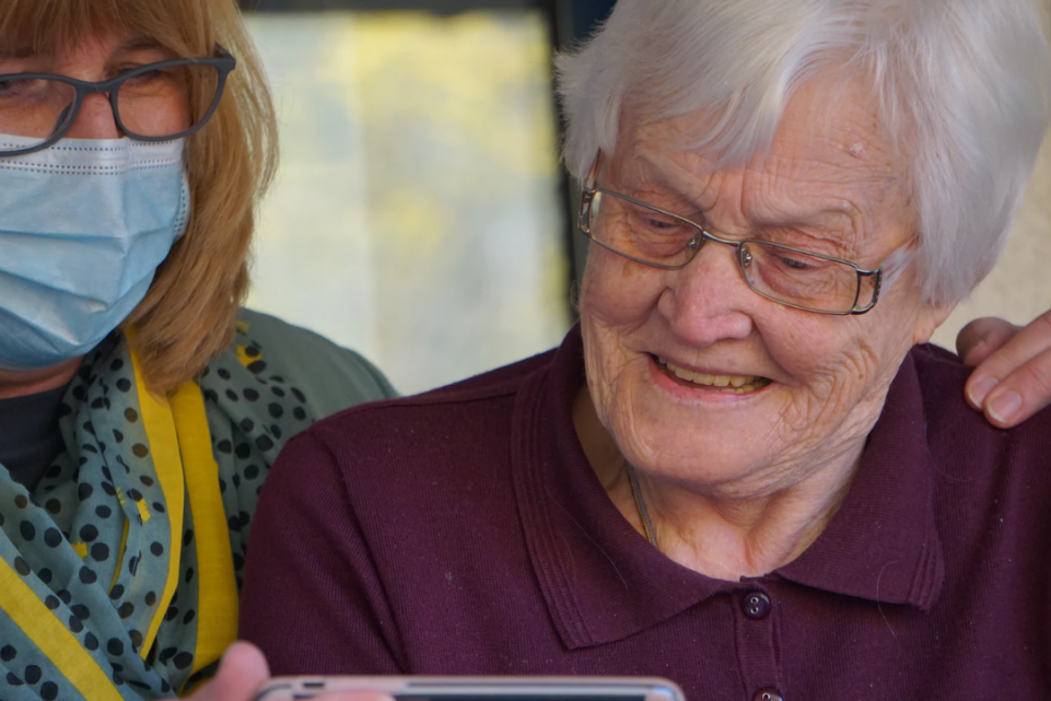 A woman in a face mask showing an elderly woman a video clip on a phone