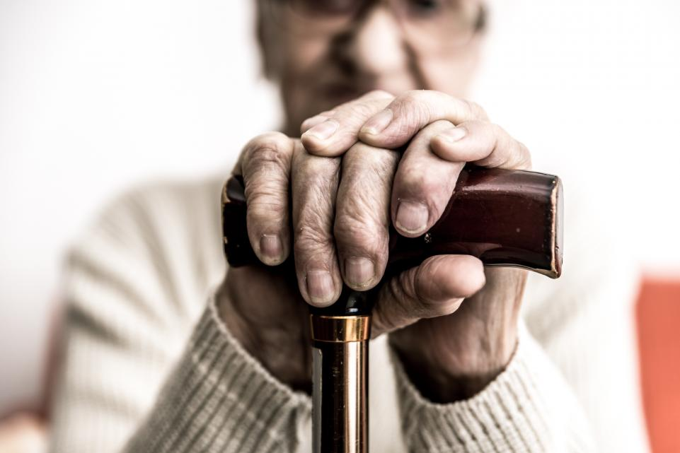 Close up of the hands of an elderly man with a cane
