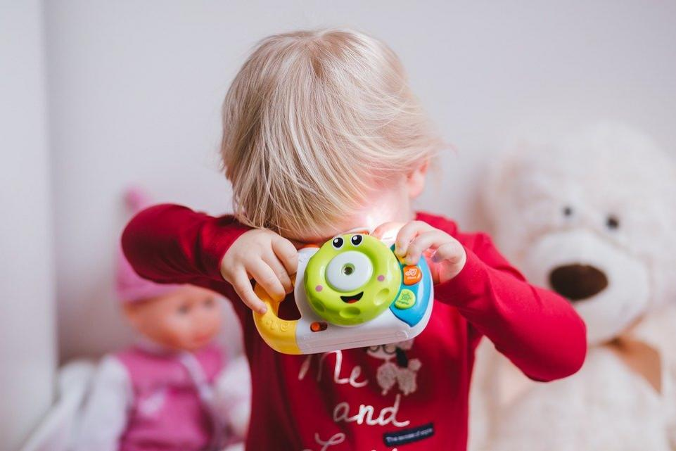Child covering face with a toy
