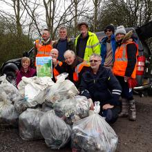 Older volunteers litter picking with large bags of rubbish