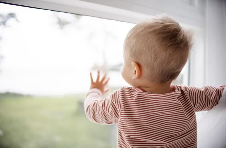 child in red striped shirt looking out the window