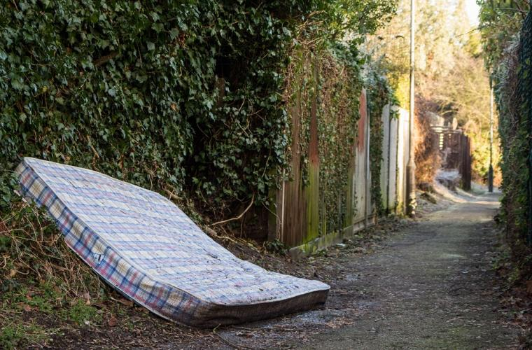 Mattress lying on the side of a road