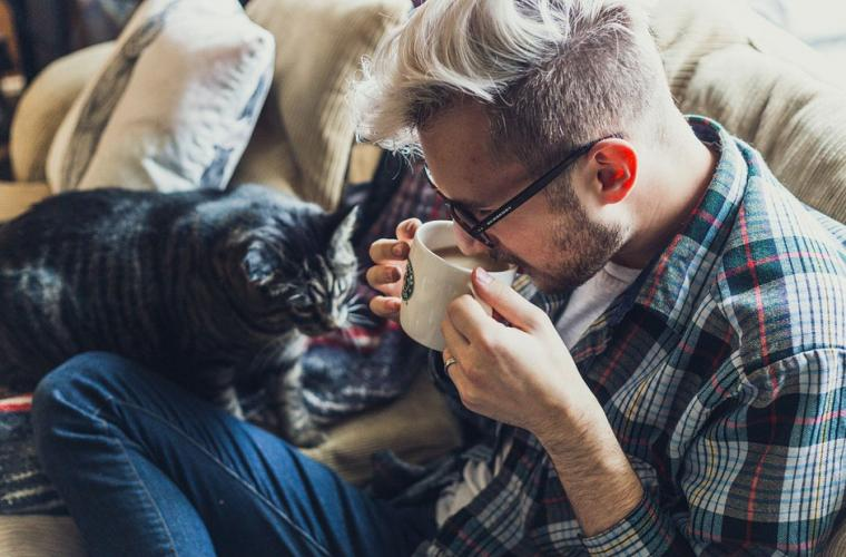 Man sitting on sofa with his cat