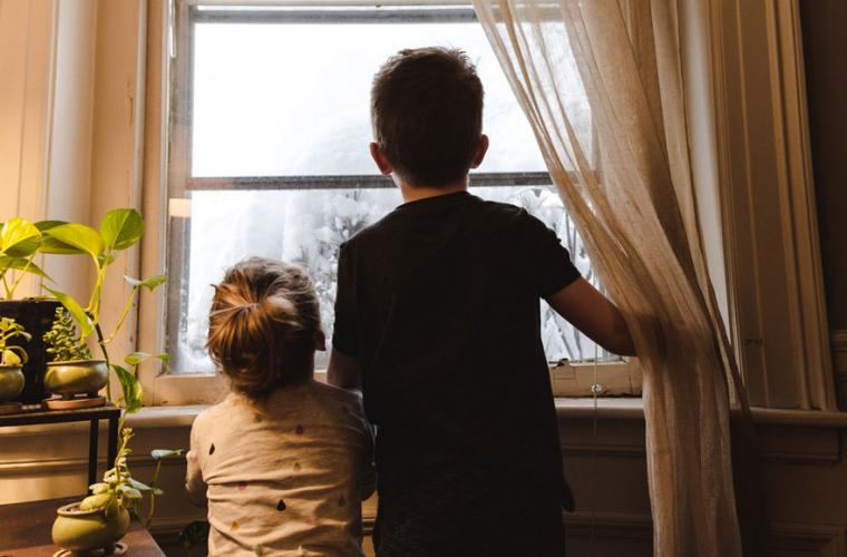 Two boys looking out window