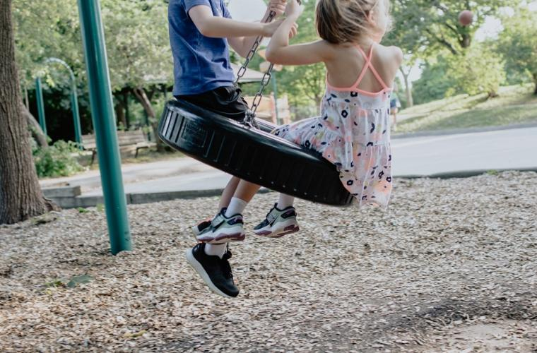 boy in green top and girl in white dress playing on swing