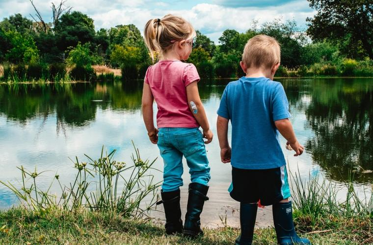 girl and boy standing on green grass near lake during daytime