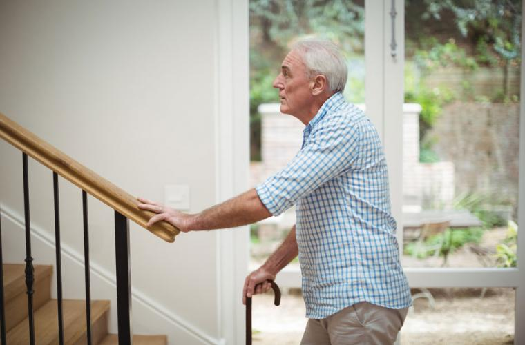 photo of old man with walking stick about to climb stairs