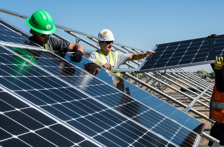 Men installing solar panels on open field
