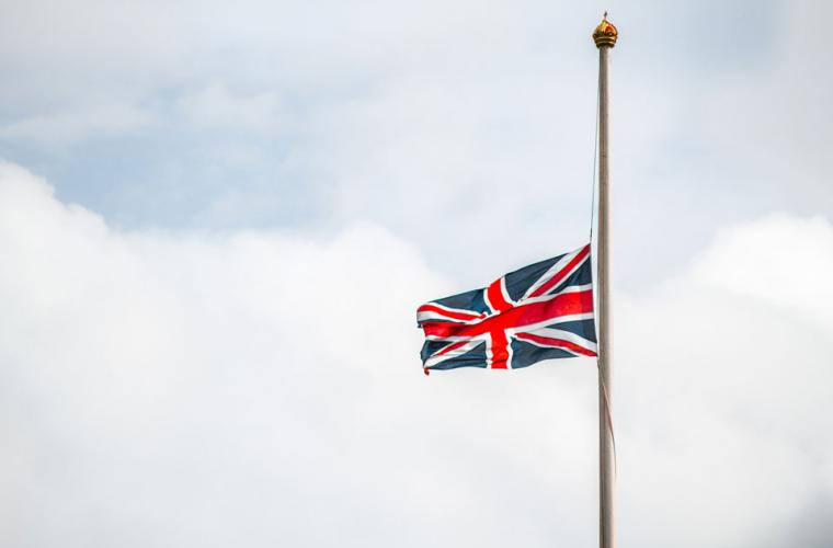 A union jack flag flown at half mast against an overcast sky