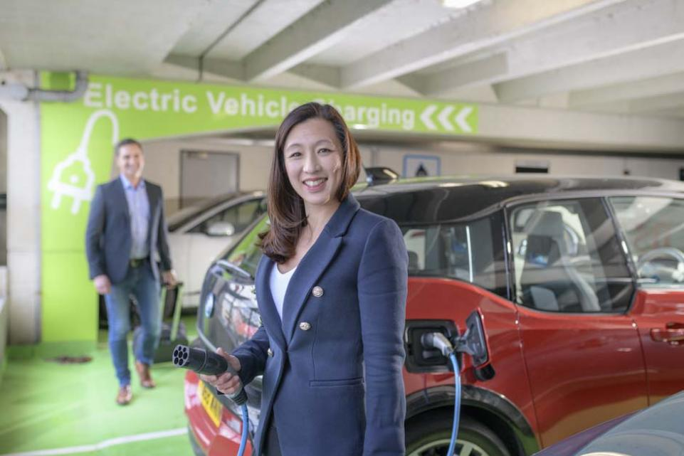 Electric vehicle - woman charging car