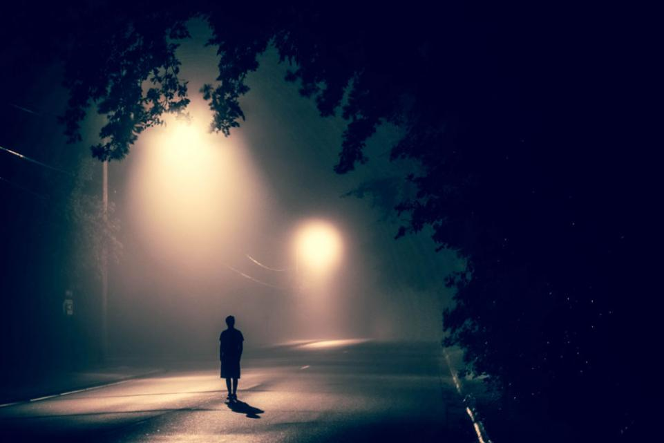 Woman walking alone in the middle of the street at night