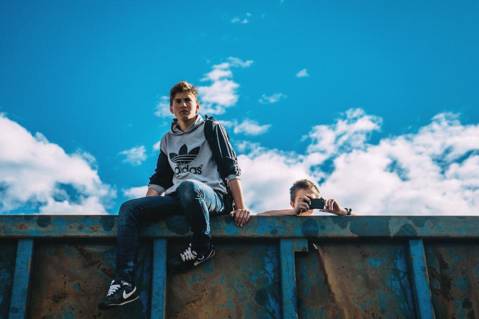 Photo of teenagers sitting on rubbish container