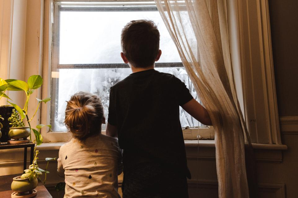 Boy and girl looking out of window