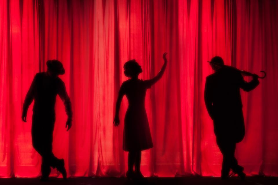 Three silhouettes on stage