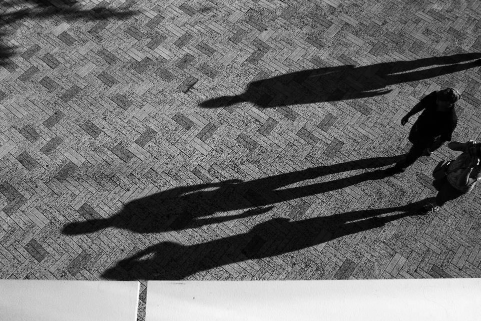 People walking causes a long shadow