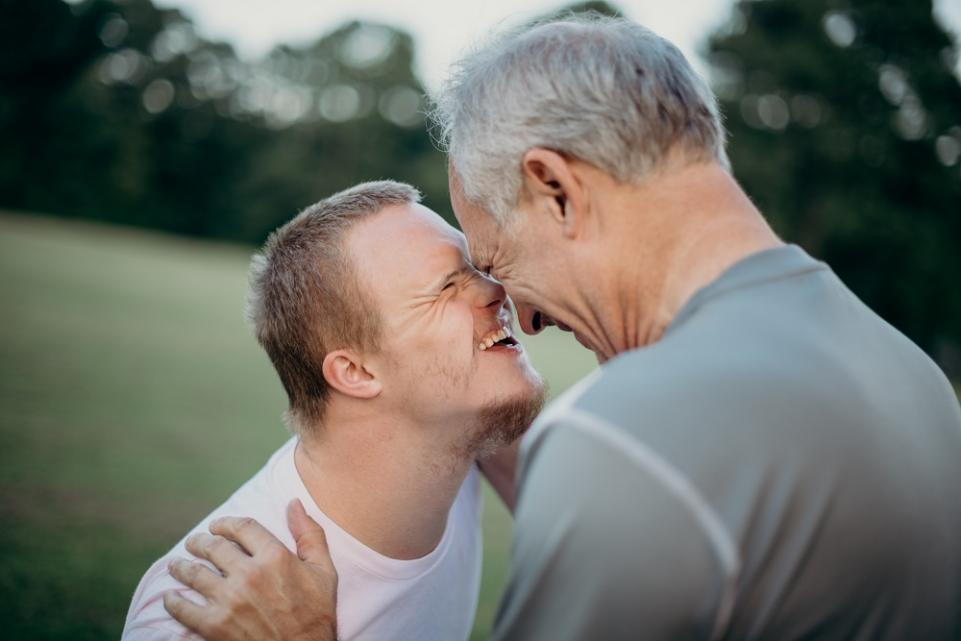 Two men, one older and one younger with Down's Syndrome, smiling at each other on a grass field
