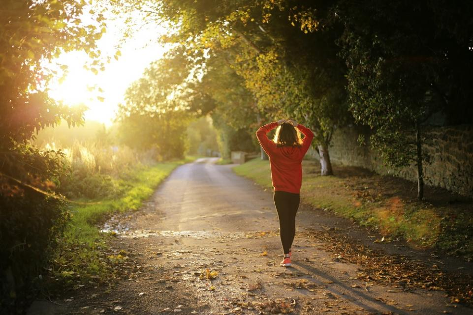 A young woman out jogging in the country side during sunset
